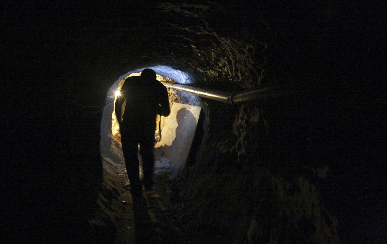 """A journalist walks through a tunnel during a presentation to the media in Tijuana November 16, 2011. Police have discovered a """"major cross-border drug tunnel"""" running to California from Mexico, and seized 14 tons of marijuana, authorities said Wednesday. The tunnel links warehouses in an industrial park south of San Diego and the Mexican border city of Tijuana, the U.S. Immigration and Customs Enforcement agency said in a news release. REUTERS/Jorge Duenes (MEXICO - Tags: CRIME LAW DRUGS SOCIETY)"""