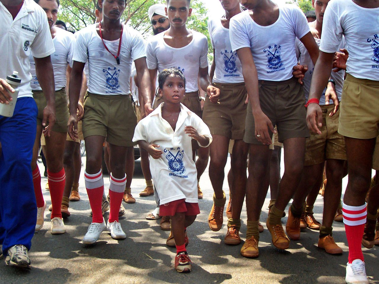 """Ik heb heerlijk gerend vandaag. Ik kan zoveel rennen als ik wil"", zei Budhia Singh (4) nadat hij 7 uur had hardgelopen. Foto AP, Biswaranjan Rout Budhia Singh, 4, runs along with soldiers in Bhubaneswar, in the eastern Indian state of Orissa, Tuesday, May 2, 2006. Cheered by thousands, Singh ran 65 kilometers (40 miles) Tuesday to enter the country's foremost record book. Singh, a slum resident from Orissa whose talent was discovered by a local sports coach, was escorted by doctors and 300 paramilitary cadets of the Central Reserve Police Force which plans to sponsor his upbringing. (AP Photo/Biswaranjan Rout)"