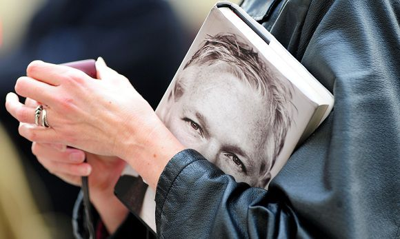 Caption: A woman holds a copy of book entitled 'Julian Assange: The Unauthorised Biography' outside London's High Court on November 2, 2011. WikiLeaks founder Julian Assange attended court in London on Wednesday to hear whether he will be extradited to Sweden to face questioning over allegations of rape and sexual assault. AFP PHOTO/LEON NEAL