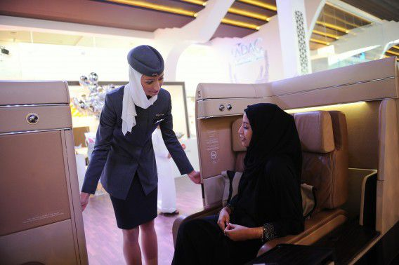 An Etihad flight attendant helps a visitor sit in a mock cabin lounge seat during the World Route Development Strategy Summit at Abu Dhabi National Exhibition Centre, September 30, 2012. Etihad Airways, the Abu Dhabi-based carrier which has been on a recent acquisition spree, is eyeing further investments if the right opportunity arises, its chief executive said on Sunday, adding 2012 revenue could top $5 billion for the first time. REUTERS/Ben Job (UNITED ARAB EMIRATES - Tags: TRANSPORT BUSINESS)