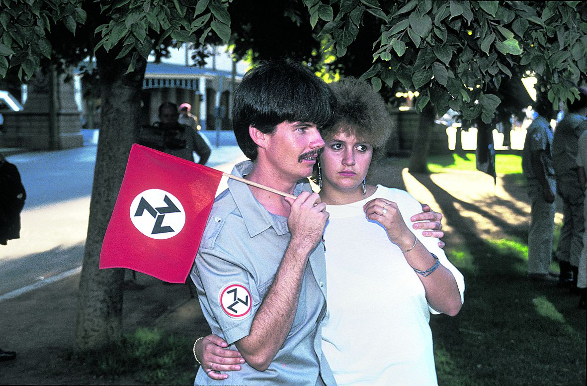 South Africa, Pretoria. 1991. Caption: A member of the ultra right-wing group, the AWB (Afrikaanse Weerstandsbeweging), attends a rally with his girlfriend in Pretoria. The flag has many design elements in common with the Swastika, however members of the organization state that the triple seven component has a biblical reference.