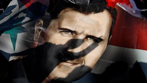 Caption: Shadows of Syrians are reflected on a giant poster showing President Bashar Assad, during a supporting rally in Damascus, Syria, Friday, Dec. 16, 2011. Syrian security forces opened fire on anti-government protesters after Friday prayers at several locations around the country, while the army sent reinforcements into a southern area where military defectors recently launched deadly attacks on regime troops. (AP Photo/Muzaffar Salman)
