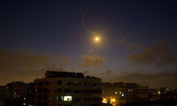 Een lichtflits boven Gazastad. Israël viel vannacht doelen aan van Hamas in de Gazastrook.