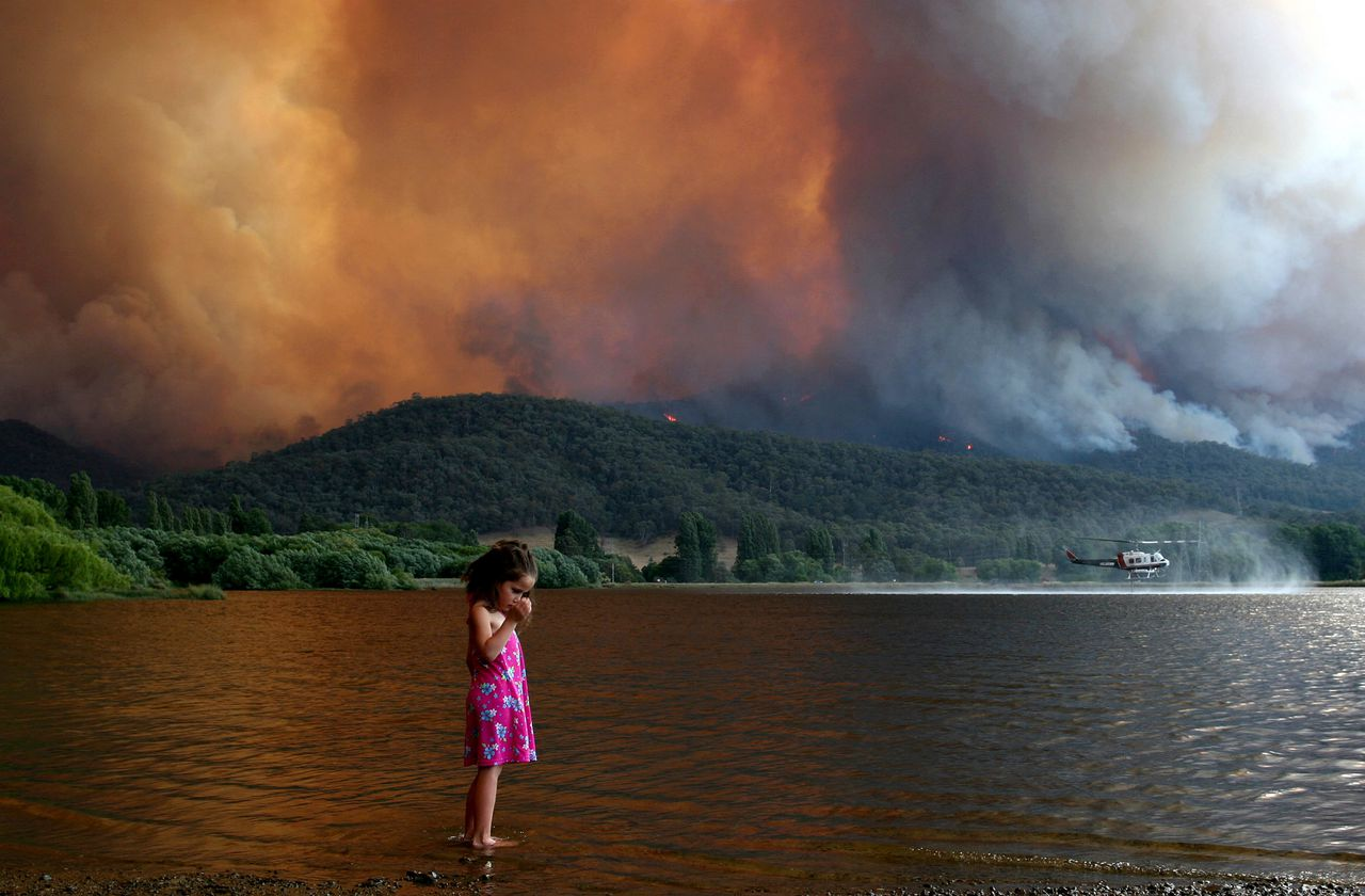 Pootje baden aan de voet van Mount Beauty in Victoria, terwijl een blushelikopter 'bijtankt'. Foto AP Milan Smith wets her feet at the Mt Beauty pondage as a fire-fighting helicopter refills its water tank in Mt Beauty, Victoria, Sunday, Dec. 10, 2006. Fires continue to burn across the state and have already razed more than 250,000 (617,750 acres) of alpine and farm land (AP Photo/AAP Image, Chris Hocking) **AUSTRALIA OUT, NEW ZEALAND OUT, MAGS OUT, NO SALES, ONLINE OUT, ONE TIME USE ONLY **