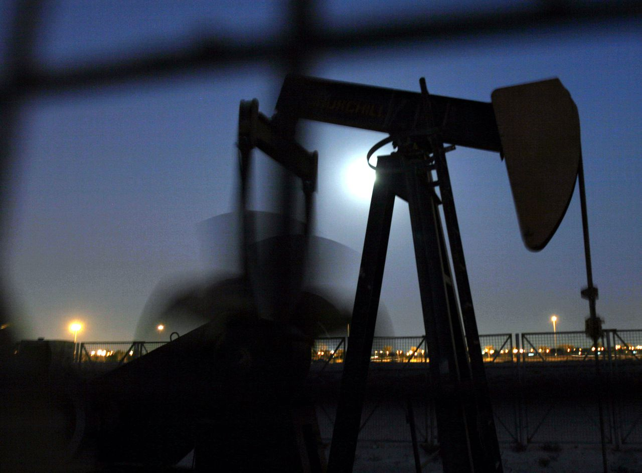 Een ja-knikker pompt olie op in het emiraat Bahrein. Foto AP An oil pump works in the moonlight Wednesday, Nov. 12, 2008, in the oilfields of Sakhir, Bahrain, in the Persian Gulf. Oil prices dropped below $57 a barrel Wednesday on fears of stagnating global growth. Oil prices have plunged more than 60 percent in four months despite two recent OPEC production cuts. (AP Photo/Hasan Jamali)
