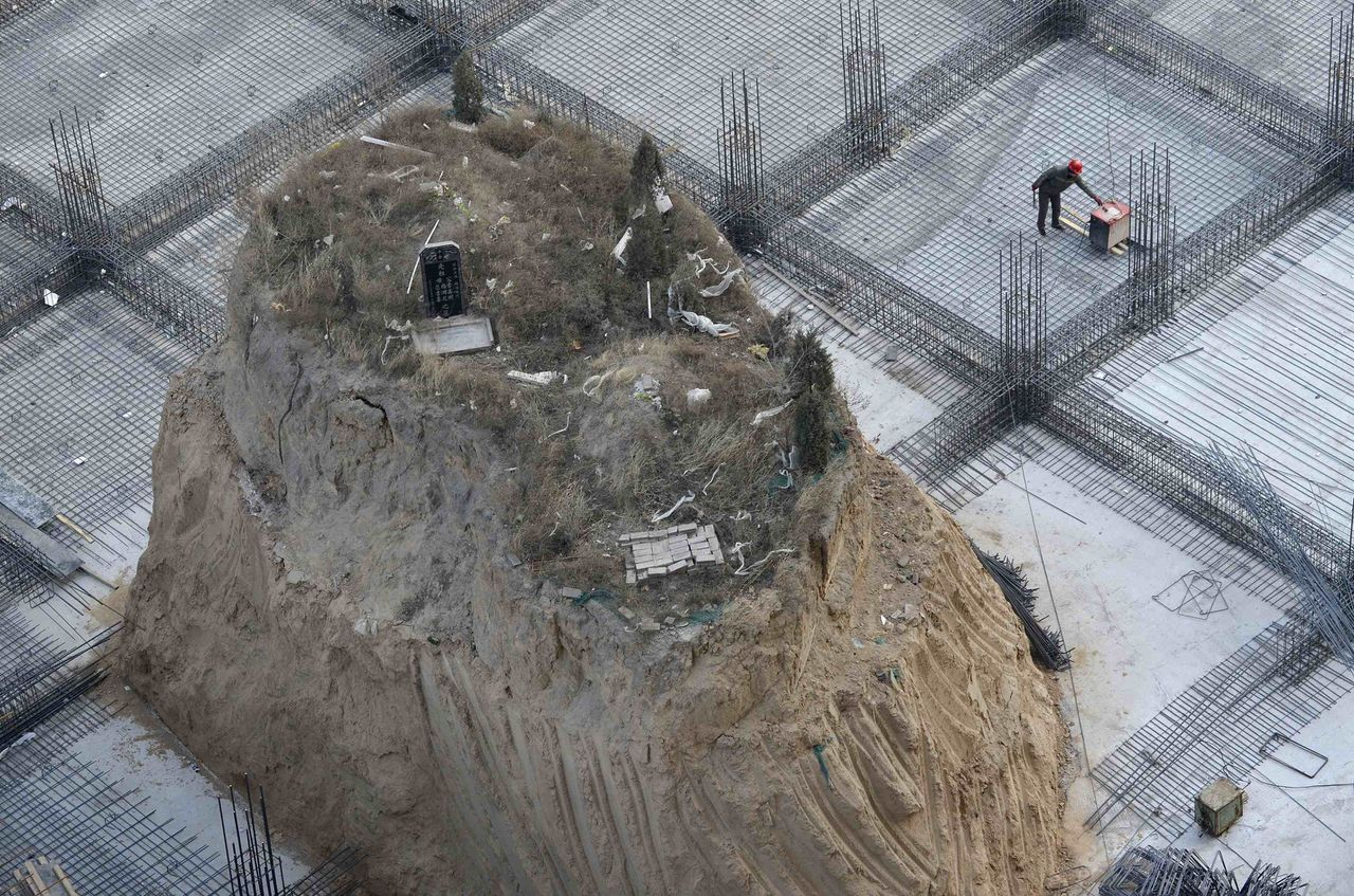 An ancestral tomb, measuring 10 metres high and a surface area of 10 square metres, is seen on the construction site of a building in Taiyuan, Shanxi province, December 6, 2012. The grave, which is believed to have existed since 2004, has not been moved as the family of the deceased is waiting for an auspicious date to do so and a reason from the developer of choosing this site, according to the owner of tomb. The building is scheduled to be completed by April 2013. REUTERS/Stringer (CHINA - Tags: SOCIETY REAL ESTATE BUSINESS) CHINA OUT. NO COMMERCIAL OR EDITORIAL SALES IN CHINA