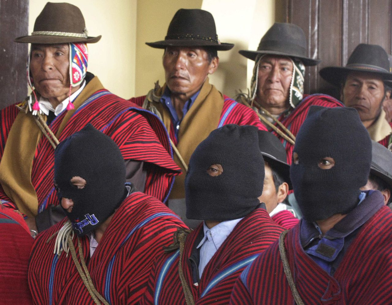 De Ponchos Rojos op een bijeenkomst vorige maand waar zij wapens inleverden in ruil voor vee. Foto AFP Masked members of the Ponchos Rojos pressure group aligned with Bolivia's leftist President Evo Morales attend a meeting with government officials in Ancoraimes, about 180 km (110 miles) north of La Paz, July 9, 2008. The Ponchos Rojos offered to relinquish their weapons to Bolivian army officers as a sign that they do not intend to battle with Morales' opponents in the relatively-prosperous east of the country. REUTERS/Gaston Brito (BOLIVIA)