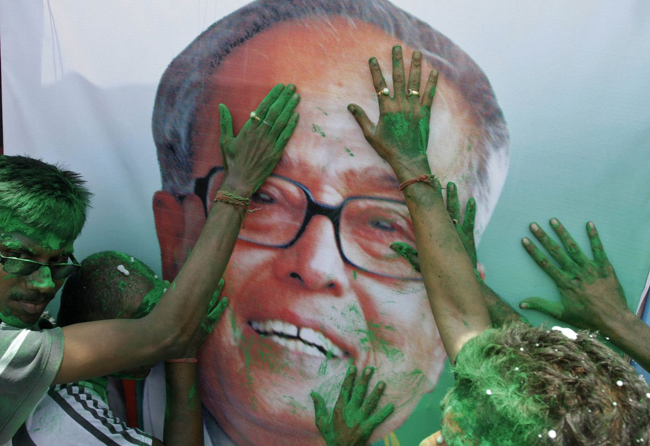 Activists of India's ruling Congress party apply colored powder on portrait of Pranab Mukherjee, as they celebrate his victory in India's presidential election in Kolkata, India, Sunday, July 22, 2012. Former Finance Minister Pranab Mukherjee, the candidate from India's governing Congress party, has claimed victory in the election for the country's next president, a largely ceremonial position. His rival, Purno Agitok Sangma, conceded defeat. (AP Photo/Bikas Das)