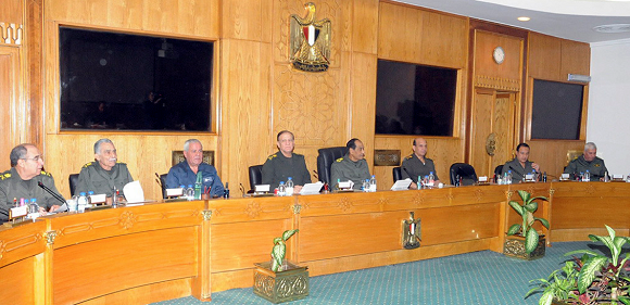 Caption: Field Marshal Mohamed Hussein Tantawi (4th L), the head of the ruling Supreme Council of the Armed Forces (SCAF), and chief of staff of the Egyptian armed forces Sami Anan sit with assistants before The Egyptian official news agency, political figures and representatives, at a meeting in Cairo November 22, 2011. Egyptians frustrated with military rule battled police in the streets again on Tuesday as the generals scrambled to cope with the cabinet's proffered resignation after bloodshed that has jolted plans for Egypt's first free election in decades. REUTERS/Middle East News Agency (MENA)/Handout (EGYPT - Tags: CIVIL UNREST POLITICS MILITARY) FOR EDITORIAL USE ONLY. NOT FOR SALE FOR MARKETING OR ADVERTISING CAMPAIGNS. THIS IMAGE HAS BEEN SUPPLIED BY A THIRD PARTY. IT IS DISTRIBUTED, EXACTLY AS RECEIVED BY REUTERS, AS A SERVICE TO CLIENTS