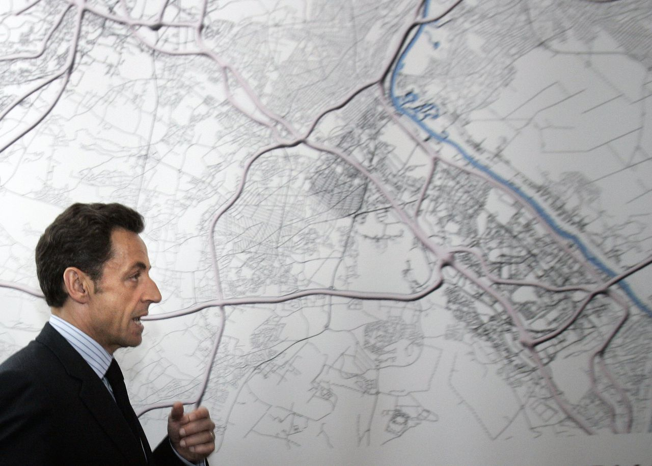 """Nicolas Sarkozy op de opening van Le Grand Paris Foto AFP French President Nicolas Sarkozy visits the Great Paris"""" exhibition on April 29, 2009 at the Architecture Museum in Paris, after oulining plans for an overhaul of transport and design in the capital and its suburbs, to create a dynamic new """"Greater Paris"""" region. French President Nicolas Sarkozy has unveiled an ambitious, costly new plan to rethink the structure of Paris and its troubled suburbs. Ten architect cabinets presented blueprints aimed at adapting the Paris metropolitan area to modern needs. AFP PHOTO POOL FRANCOIS MORI"""