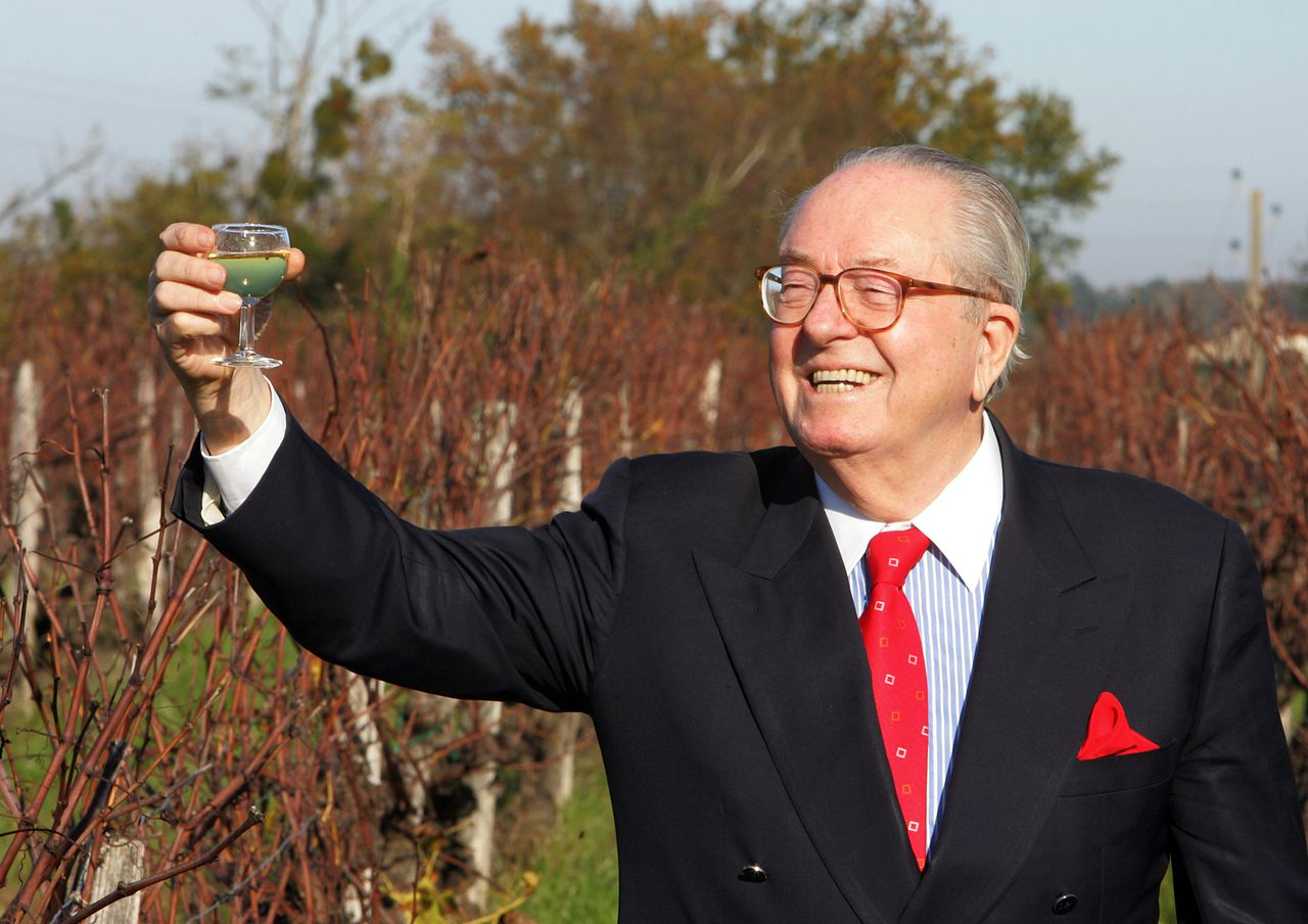 """Jean-Marie Le Pen op campagne in Loupiac in de Dordogne. (Foto AFP) French President of far-right party Front National (FN) and candidate for the 2007 presidential election Jean-Marie Le Pen (R) stands 29 November 2006 in vines with a glass of vine in Loupiac (western France). Le Pen continues this way his """"marche verte"""" (green tour), a bus tour started 15 November to meet vintners and farmers. AFP PHOTO PIERRE ANDRIEU"""