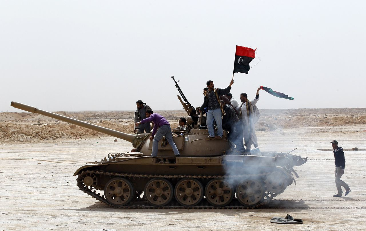 Rebels wave a Kingdom of Libya flag as they ride on top of a tank on the outskirts of Ajdabiyah, on the road leading to Brega, March 2, 2011. The flag which was used when Libya gained independence from Italy in 1951, has been used as a symbol of resistance against Libya's leader Muammar Gaddafi in the recent protests. REUTERS/Goran Tomasevic (LIBYA - Tags: CIVIL UNREST MILITARY POLITICS IMAGES OF THE DAY)