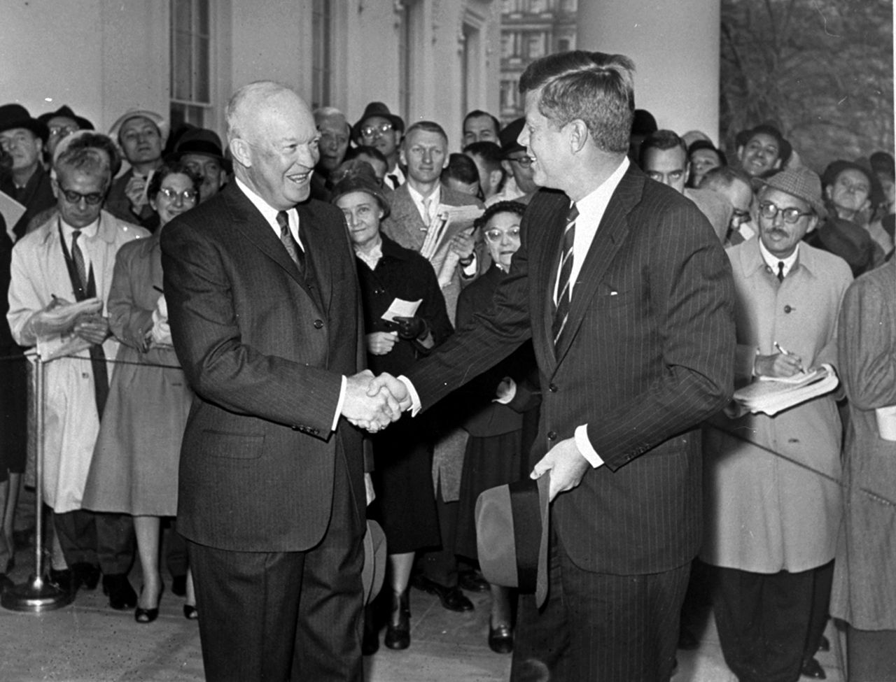 """President Eisenhower verwelkomt op 6 december 1960 de aanstaande president Kennedy op het Witte Huis. Foto AP ** FILE ** In this Dec. 6, 1960 file photo, President Eisenhower shakes hands with President-elect John F. Kennedy as he arrives at the White House in Washington. After the three-hour meeting, an aide later described Eisenhower as """"overwhelmed by Senator Kennedy, his understanding of the world problems, the depth of his questions, his grasp of the issues and the keenness of his mind."""" (AP Photo, File)"""