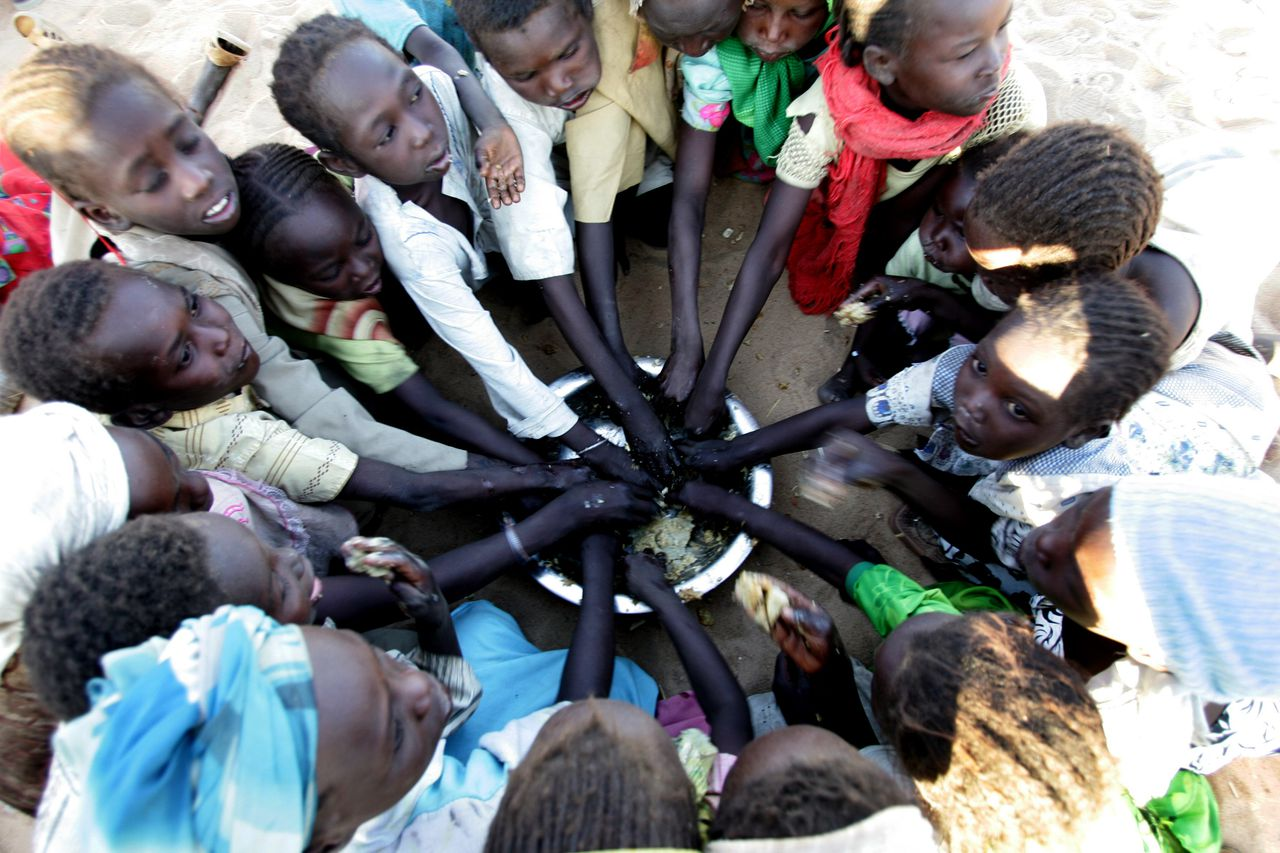 Kinderen krijgen te eten in een ontheemdenkamp in Nyala, in de West-Soedanese regio Darfur. Foto AFP (FILES) Displaced Sudanese children eat at the Sakali Displaced Persons camp in the city of Nyala in Sudan's strife-torn Darfur region February 21, 2007. Oxfam launched an urgent appeal to mark UN World Food Day on October 16, 2008 saying the financial crisis had sent food costs soaring and the global total of people in hunger to nearly one billion people. The British-based aid and development charity said rising food prices had pushed an extra 119 million people into hunger, meaning 967 million people were now living below the hunger line. AFP PHOTO / MUSTAFA OZER