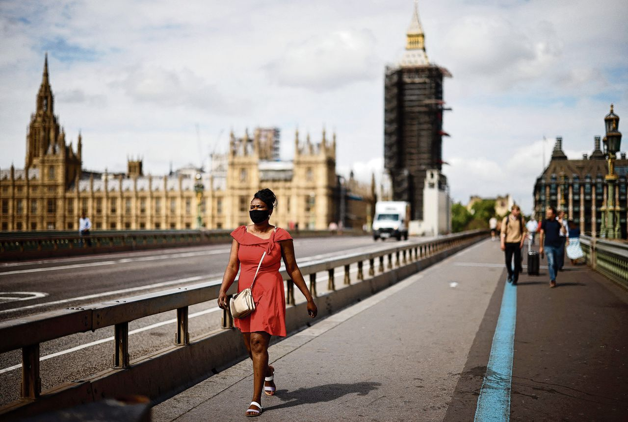 TOPSHOT - A pedestrian wearing a face covering walks over Westminster Bridge near the Houses of Parliament in central London on June 7, 2021. - The Delta variant of the coronavirus, first discovered in India, is estimated to be 40 percent more transmissible than the Alpha variant that caused the last wave of infections in the UK, Britain's health minister said Sunday. (Photo by Tolga Akmen / AFP)