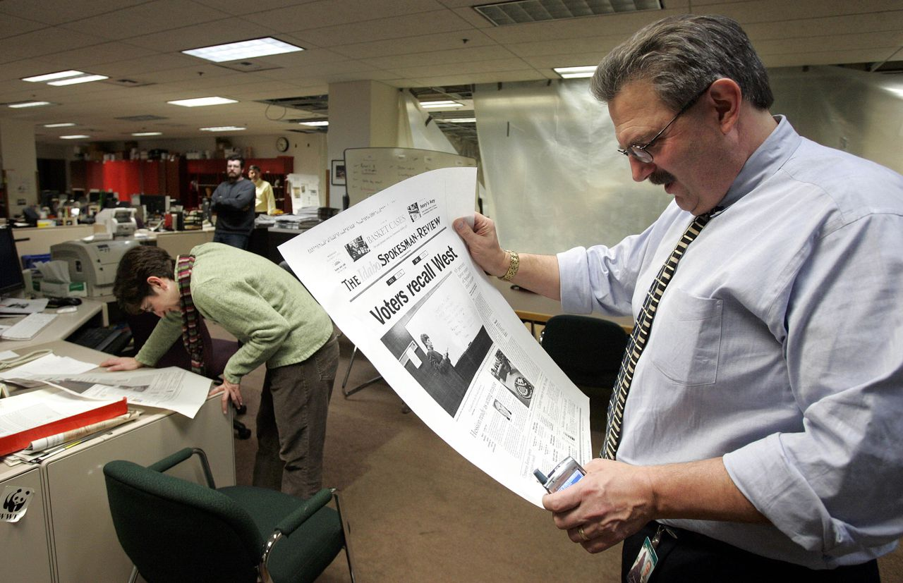 Spokesman-Review editor Steve Smith, right, and city editor Carla Savalli look over page one mock-ups for the following day's edition in the newspaper's newsroom following a special recall election of Spokane Mayor Jim West, Tuesday, Dec. 6, 2005, in Spokane, Wash. The Spokesman-Review newspaper conducted an undercover investigation and reported in a series of articles beginning May 5 that West was a closeted homosexual who visited gay chat rooms on his city-owned computer and offered internships and other favors to young men he hoped to have sex with. (AP Photo/Elaine Thompson)