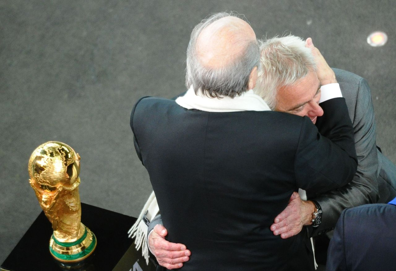 Sepp Blatter (links) omhelst bondscoach Bert van Marwijk. Foto AFP FIFA President Sepp Blatter (L) consoles Netherlands' coach Bert Van Marwijk next to the World Cup trophy after Netherlands lost to Spain in the 2010 FIFA football World Cup final match on July 11, 2010 at Soccer City stadium in Soweto, suburban Johannesburg. Spain won the match 1-0. NO PUSH TO MOBILE / MOBILE USE SOLELY WITHIN EDITORIAL ARTICLE - AFP PHOTO / CHRISTOPHE SIMON