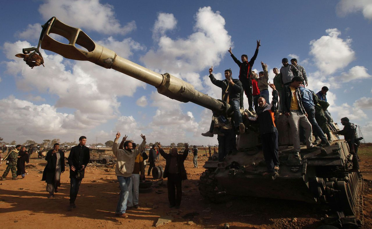 "ATTENTION EDITORS: CAPTION CORRECTION - CORRECTING TYPE OF VEHICLE. People celebrate atop a destroyed mobile artillery piece belonging to forces loyal to Libyan leader Muammar Gaddafi after an air strike by coalition forces, along a road between Benghazi and Ajdabiyah March 20, 2011. Western forces pounded Libya's air defences and patrolled its skies on Sunday, but their day-old intervention hit a serious diplomatic setback as the Arab League chief condemned the ""bombardment of civilians"". REUTERS/Suhaib Salem (LIBYA - Tags: POLITICS CIVIL UNREST IMAGES OF THE DAY)"