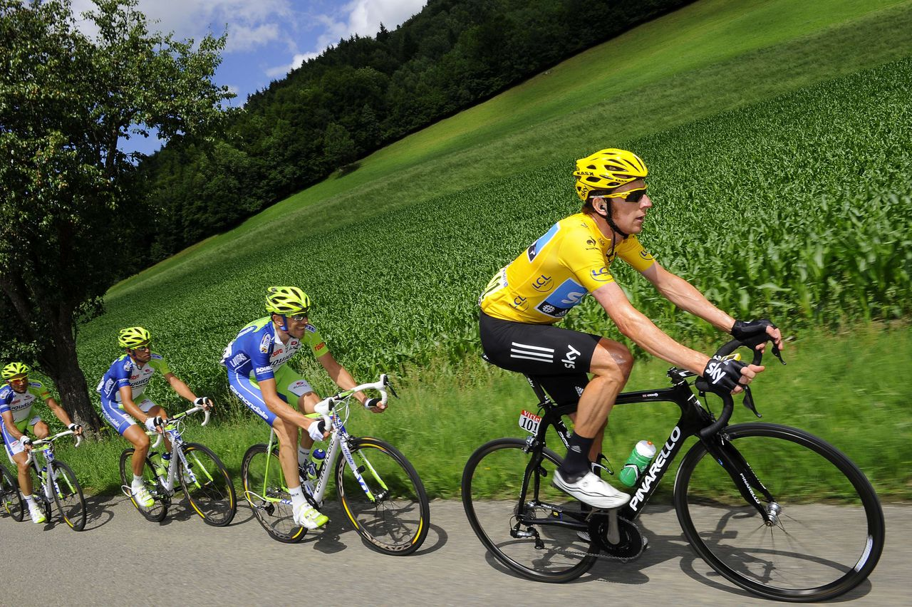 TOPSHOTS Overall leader's yellow jersey, British Bradley Wiggins (R) rides with Italy's Ivan Basso (L) in the 157,5 km and eighth stage of the 2012 Tour de France cycling race starting in Belfort and finishing in Porrentruy, Switzerland, on July 8, 2012. AFP PHOTO / LIONEL BONAVENTURE