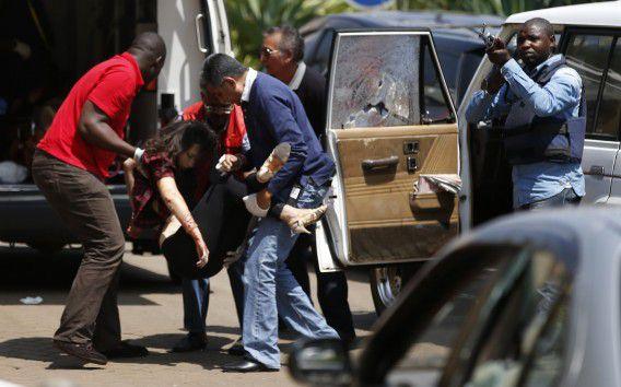 Een vrouw wordt weggedragen richting een ambulance, terwijl de Keniaanse politie jacht maakt op de daders.