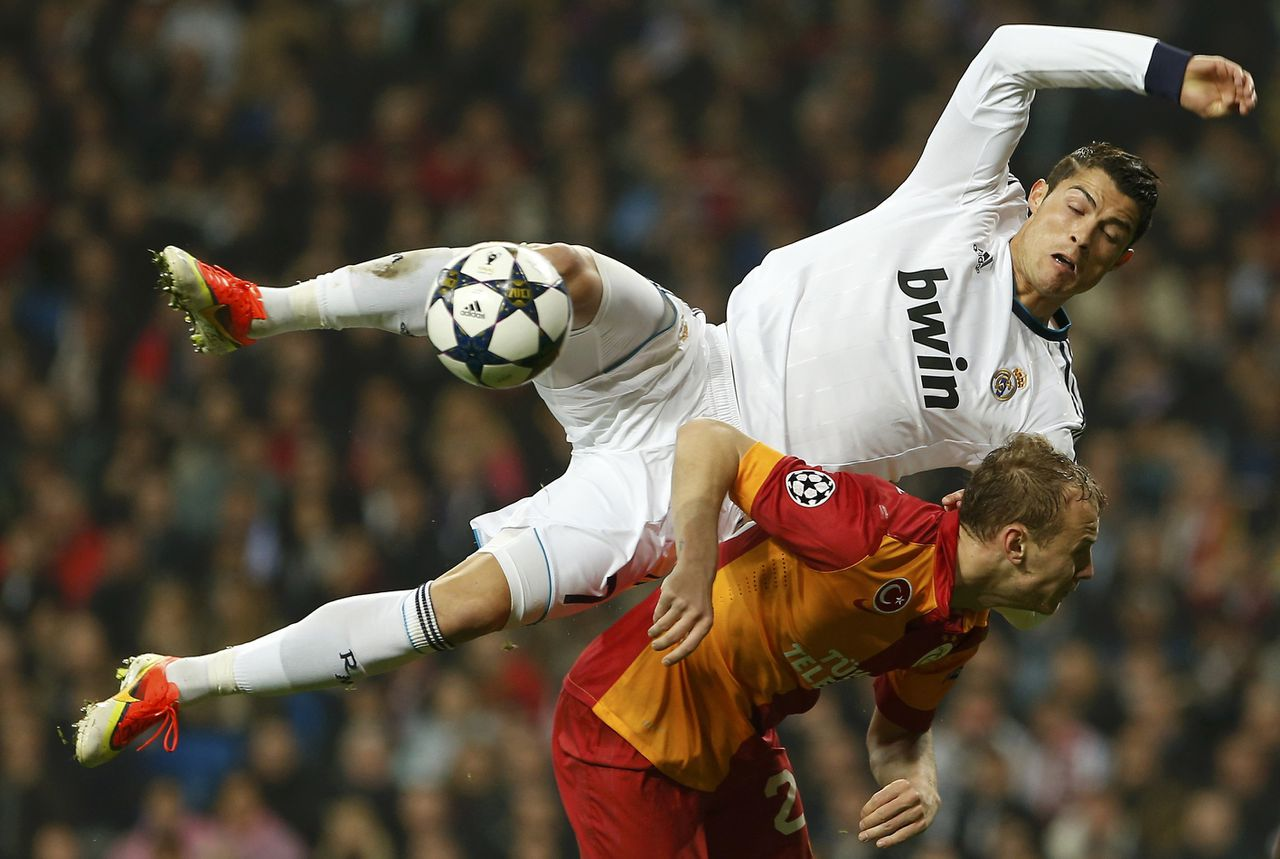 Real Madrid's Cristiano Ronaldo disputs a ball over Galatasaray's Semih Kaya during Champions League quarter-final, first leg soccer match at Santiago Bernabeu stadium in Madrid April 3, 2013. REUTERS/Susana Vera (SPAIN - Tags: SPORT SOCCER TPX IMAGES OF THE DAY)