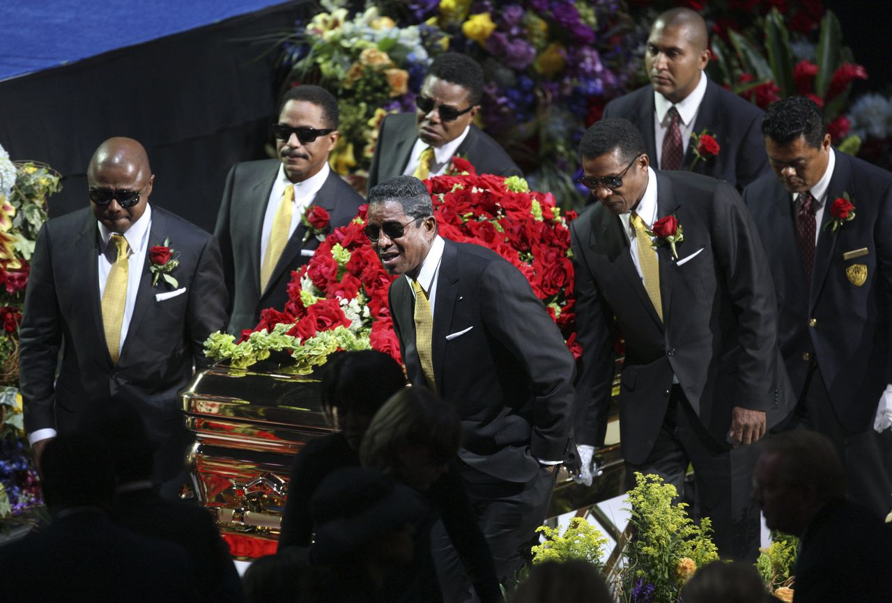Familie draagt de kist met het lichaam van Jackson uit het Staples Center (Foto AFP) The Jackson brothers (L-R) Randy, Marlon, Tito, Jermaine and Jackie carry the casket from the memorial services for pop star Michael Jackson at the Staples Center in Los Angeles on July 7, 2009. AFP PHOTO/Mario Anzuoni/Pool