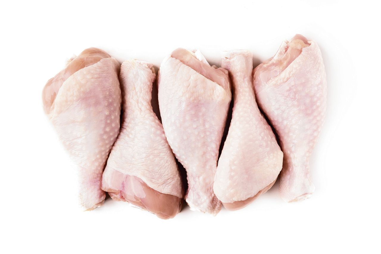 Uncooked chicken legs in row isolated on white background, top view