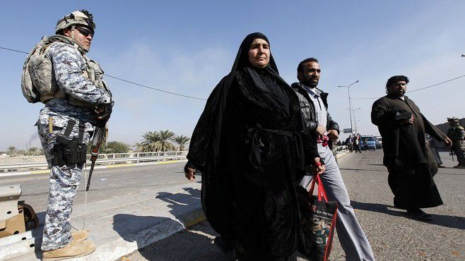 A policeman (L) provides security for Shi'ite pilgrims marching to attend the religious ceremony of Arbain, in Baghdad January 20, 2011. A roadside bomb killed one Shi'ite pilgrim and wounded nine others, in Baghdad's southern Doura district, an Interior Ministry source said. The pilgrims were walking to the holy Shi'ite city of Kerbala to commemorate the religious event of Arbain. REUTERS/Mohammed Ameen (IRAQ - Tags: RELIGION)