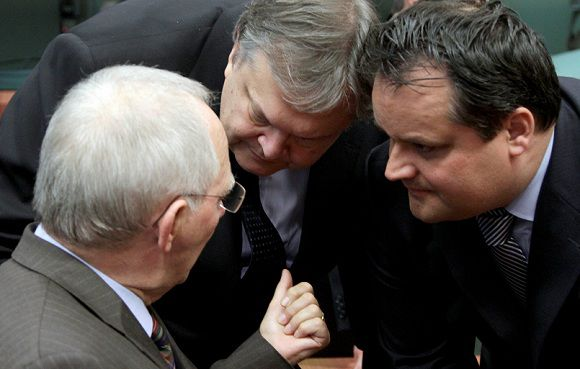 """Caption: German Finance Minister Wolfgang Schaeuble, left, speaks with Greek Finance Minister Evangelos Venizelos, center, and Dutch Finance Minister Jan Kees De Jager during a meeting of eurozone finance ministers in Brussels on Friday, Oct. 21, 2011. The chairman of the eurogroup of finance ministers says the delay to a debt crisis creates a """"disastrous"""" image of the eurozone to the outside world. Jean-Claude Juncker, who is also the prime minister of Luxembourg, added that it's not necessarily just France and Germany that have differences of opinion on how to tackle the crisis. (AP Photo/Virginia Mayo)"""