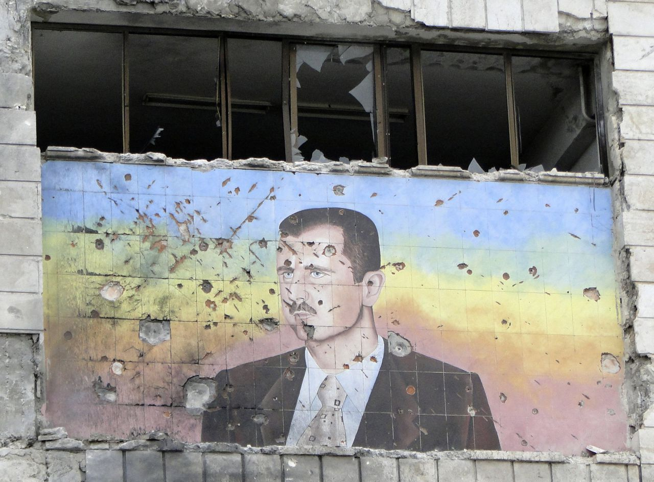 A picture of Syria's President Bashar al-Assad riddled with holes is seen on the facade of the police academy in Aleppo, after it was captured by Free Syrian Army fighters, March 4, 2013. On Sunday rebels said they captured a police academy on the outskirt of Aleppo, after days of fighting in which rebels killed 150 soldiers, while sustaining heavy casualties. REUTERS/Mahmoud Hassano (SYRIA - Tags: POLITICS CIVIL UNREST TPX IMAGES OF THE DAY)
