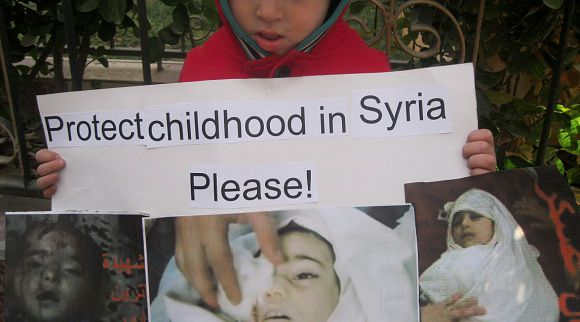 A child holds a placard during a protest against Syria's President Bashar al-Assad in Daria near Damascus December 18, 2011. Picture taken December 18, 2011. REUTERS/Handout (SYRIA - Tags: CIVIL UNREST POLITICS) FOR EDITORIAL USE ONLY. NOT FOR SALE FOR MARKETING OR ADVERTISING CAMPAIGNS. THIS IMAGE HAS BEEN SUPPLIED BY A THIRD PARTY. IT IS DISTRIBUTED, EXACTLY AS RECEIVED BY REUTERS, AS A SERVICE TO CLIENTS. TEMPLATE OUT