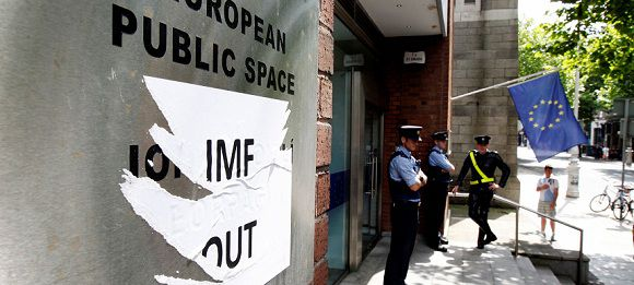 Caption: Members of the Gardai patrol outside the Dawson Street offices where the European Commission, European Central Bank and International Monetary Fund (IMF) held a joint news conference outlining Ireland's progress in meeting its targets as part of the EU/IMF bailout, in Dublin July 14, 2011. Rating agencies may be overestimating the risks associated with the current euro zone debt crisis and were it not for the contagion risk, Irish bond spreads would be narrower, a senior IMF official said on Thursday. REUTERS/Cathal McNaughton (IRELAND - Tags: BUSINESS POLITICS)