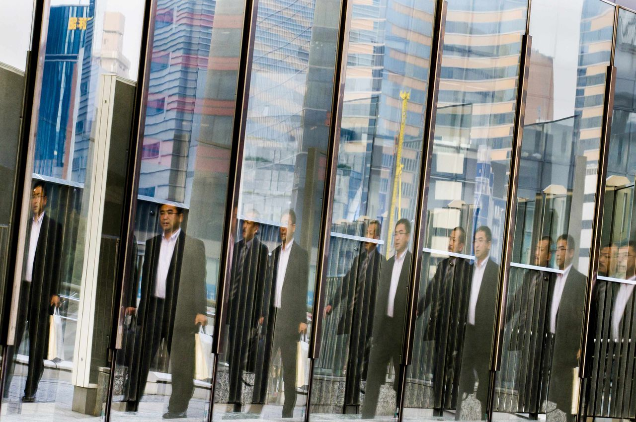 Men are reflected in a glass railing as they walk at the Shiodome business district in Tokyo November 12, 2014. Japanese companies overwhelmingly want Prime Minister Shinzo Abe to delay or scrap a planned tax increase, a Reuters poll shows, highlighting concerns that it could derail a fragile economic recovery. Picture taken November 12, 2014. REUTERS/Thomas Peter (JAPAN - Tags: BUSINESS POLITICS TPX IMAGES OF THE DAY)