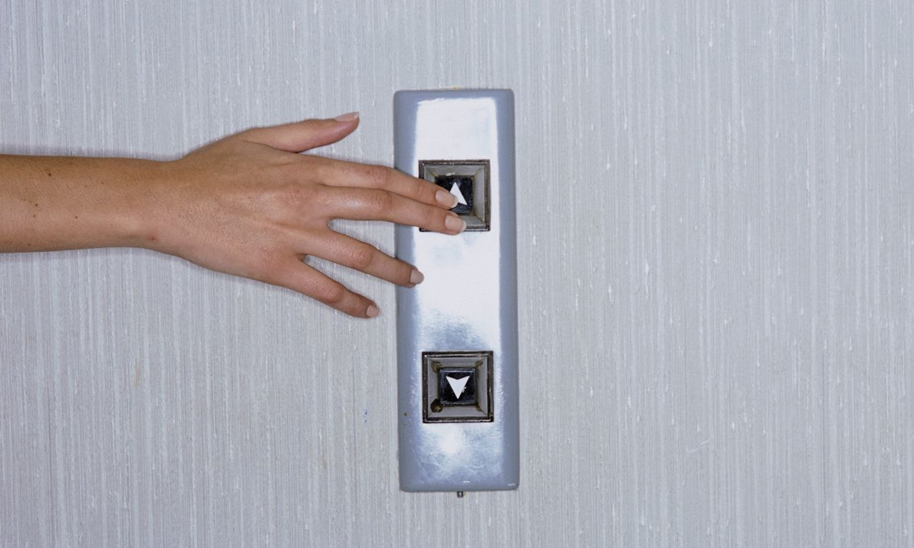 Pushing on Elevator Switch --- Image by © Reg Charity/CORBIS