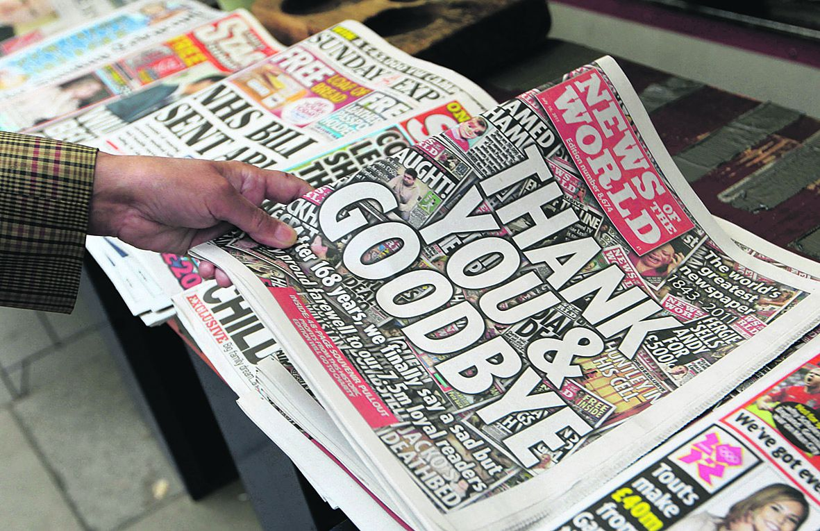"""FILE - In this July 10, 2011 file photo, a customer buys a copy of """"News of the World"""" from a newspaper vendor in central London. Britain's best-selling Sunday tabloid signed off with a simple front page message, """"Thank You & Goodbye"""", leaving the media establishment here reeling from the expanding phone-hacking scandal that brought down the muckraking newspaper after168 years. (AP Photo/Sang Tan, file)"""