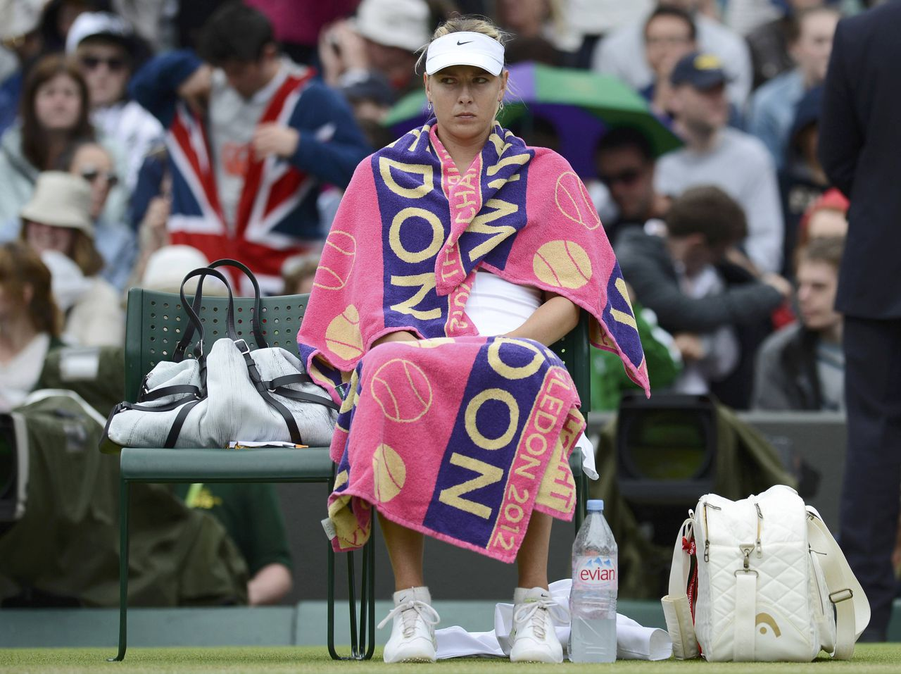 Maria Sharapova of Russia sits in her seat during a break in her women's singles tennis match against Sabine Lisicki of Germany at the Wimbledon tennis championships in London July 2, 2012. REUTERS/Dylan Martinez (BRITAIN - Tags: SPORT TENNIS)