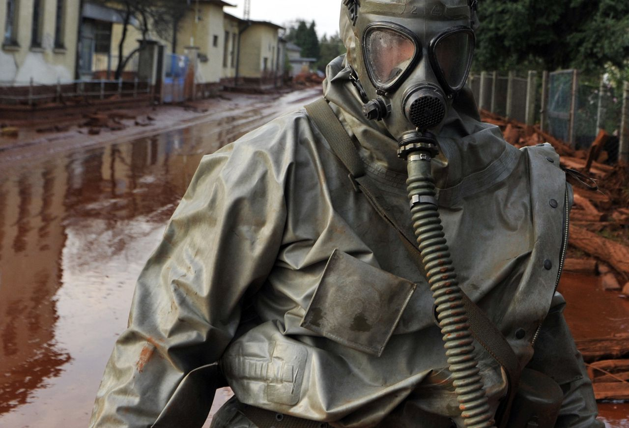 Een Hongaarse militair loopt door een straat in het dorp Devescer die overspoeld is door de modderstroom uit het afvalreservoir van een aluminiumfabriek bij Kolontár. Foto AP A Hungarian soldier wearing a chemical protection gear walks through a street flooded by toxic in the town of Devecser, Hungary, Tuesday, Oct. 5, 2010. Monday's flooding was caused by the rupture of a red sludge reservoir at an alumina plant in western Hungary and has affected seven towns near the Ajkai Timfoldgyar plant in the town of Ajka, 100 miles (160 kilometers) southwest of Budapest. (AP Photo/Bela Szandelszky)