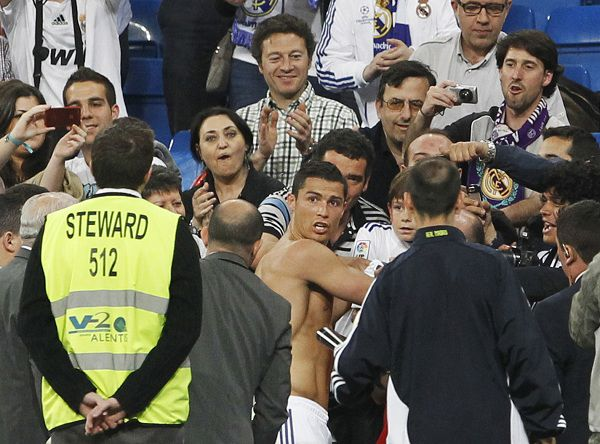 Real Madrid's Cristiano Ronaldo (C) signs autographs for fans at the end of their Spanish first division soccer match against Getafe at Santiago Bernabeu stadium in Madrid May 10, 2011. REUTERS/Susana Vera (SPAIN - Tags: SPORT SOCCER)