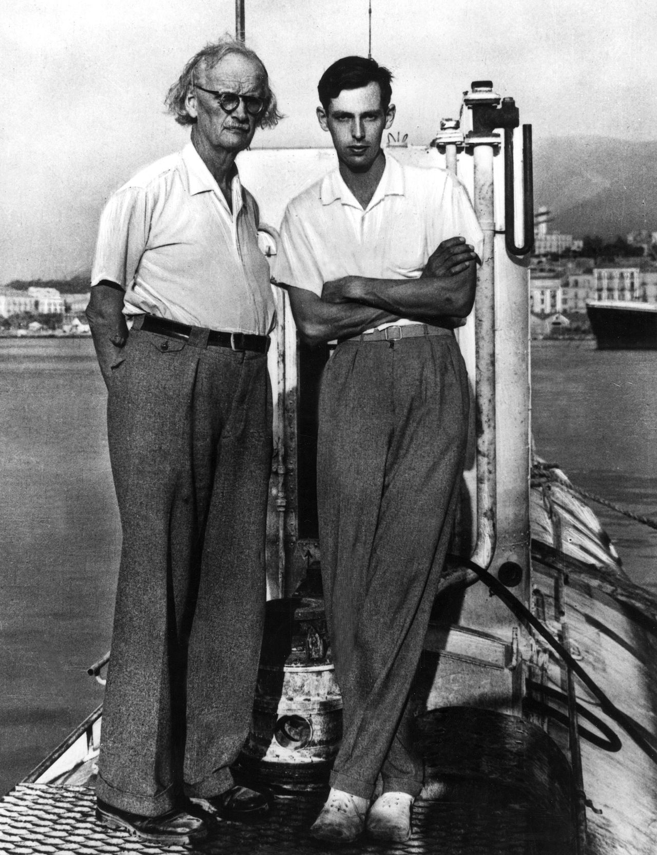 Jacques Piccard (rechts) aan dek van de Trieste, naast zijn vader Auguste. (Foto AFP) (FILES) File picture of Swiss born physicist, Auguste Piccard (L), posing with his son late deep sea explorer Jacques Piccard (R) on the deck of the Trieste bathyscaphe in the sixties. Jacques Piccard, who holds the record for travelling to the deepest point underwater, died on November 01, 2008 at the age of 86. He was born in Brussels, together with Don Walsh reached the bottom of the Mariana Trench, 10,916 metres (35,813 feet) below sea level on January 23, 1960 -- the farthest point underwater. AFP PHOTO FILES/STF (B/W ONLY)