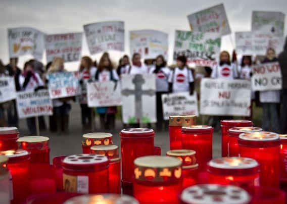 In Boekarest worden kaarsjes aangestoken voor vrouwelijke slachtoffers van huiselijk geweld door echtgenoten of partners tijdens een demonstratie eind 2011.