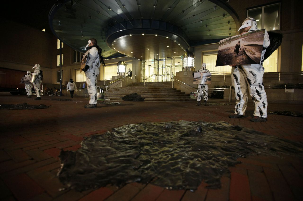 """Leden van Milieudefensie voerden gisteren actie voor het hoofdkantoor van Shell in Den Haag. Zij stellen het bedrijf verantwoordelijk voor olievervuiling in Nigeria. Foto AP Black patches representing oil spill are seen in the foreground as activists from Milieudefensie, the Dutch arm of the Friends of the Earth environmental organization, dressed up as oil-covered birds, hold pictures of oil spills in Nigeria outside Shell headquarters in The Hague, Netherlands, Wednesday Jan. 26, 2011. A Dutch parliamentary commission is meeting with Shell and environmental groups today to discuss business development in West Africa, the activists hung a banner from the building reading """"Shell, Lets' Go Clean Nigeria"""". (AP Photo/Peter Dejong)"""