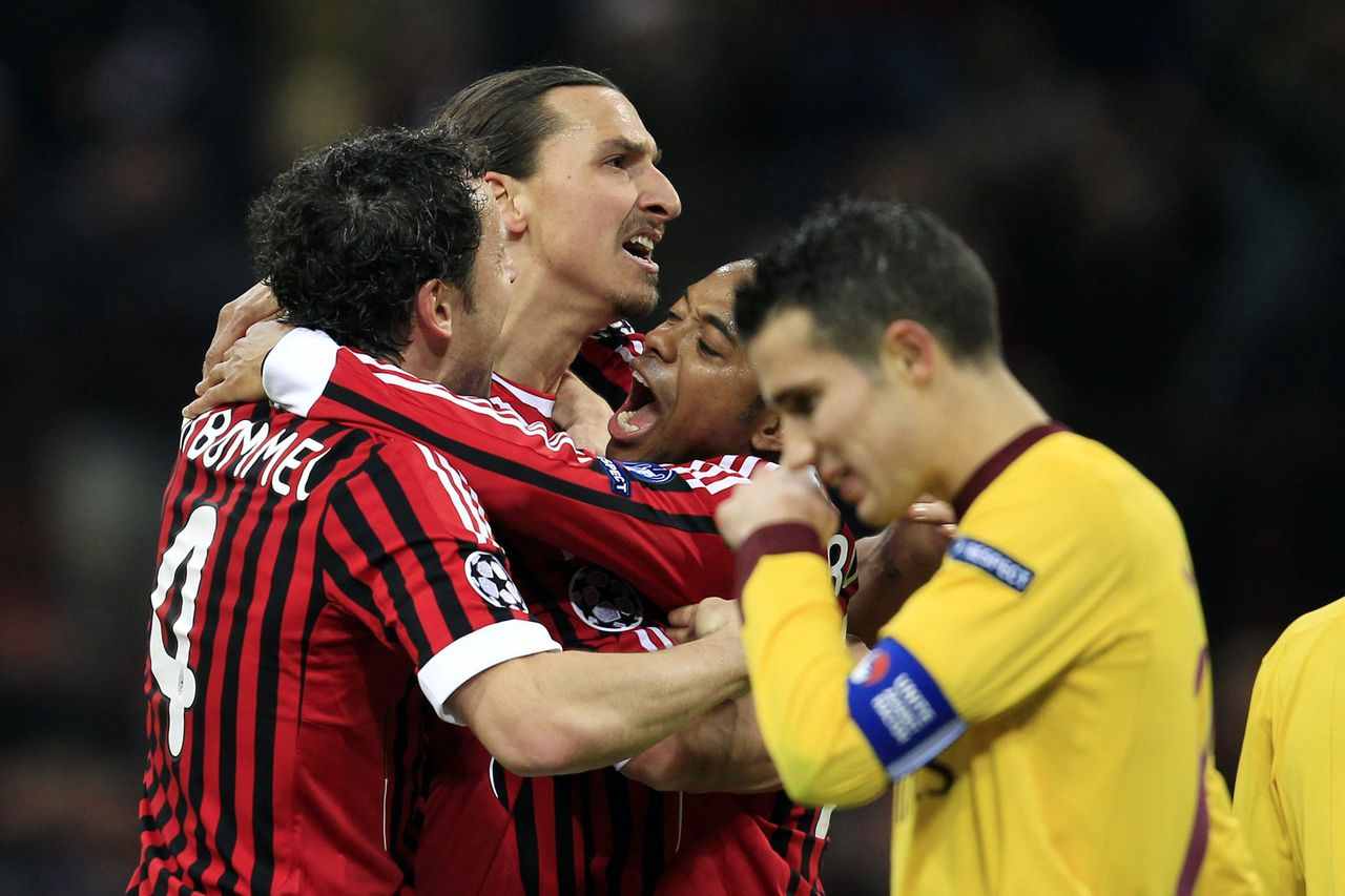 AC Milan's Zlatan Ibrahimovic (2nd L) celebrates with teammates Mark van Bommel (L) and Robinho (2nd R) as Arsenal's captain Robin van Persie reacts during their Champions League round of 16 soccer match at the Giuseppe Meazza stadium in Milan February 15, 2012. REUTERS/Stefano Rellandini (ITALY - Tags: SPORT SOCCER)