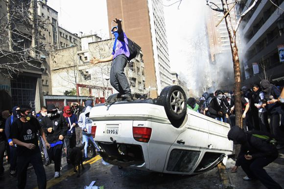 A demonstrator stands on top of an overturned car during a student protest in Santiago, Chile, Tuesday, Aug. 9, 2011. Masked demonstrators burned cars and barricades, looted storefronts and threw furniture at police as students marched by the tens of thousands to keep pressure on the government for changes in public education. Police responded with tear gas and water cannons. (AP Photo/Sebastian Silva)