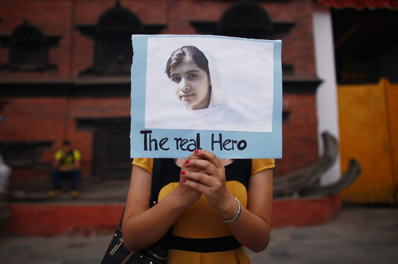 A Nepalese student holds a photo of Pakistani schoolgirl Malala Yousafzai, during a candlelight vigil to express support for her in Katmandu, Nepal, Monday, Oct.15, 2012. Yousufzai was shot along with two classmates by a Taliban gunman while they were on their way home from school on Oct. 9, 2012. (AP Photo/Niranjan Shrestha)