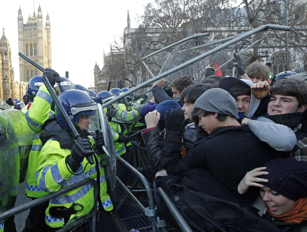 Demonstrators clash with police during a protest in Westminster, central London December 9, 2010. Britain's parliament on Thursday approved plans to increase fees paid by university students despite a rebellion by members of the coalition government. Protesters had earlier clashed with police outside parliament in central London during the debate. REUTERS/Luke MacGregor (Britain - Tags: BUSINESS CIVIL UNREST POLITICS EDUCATION SOCIETY)