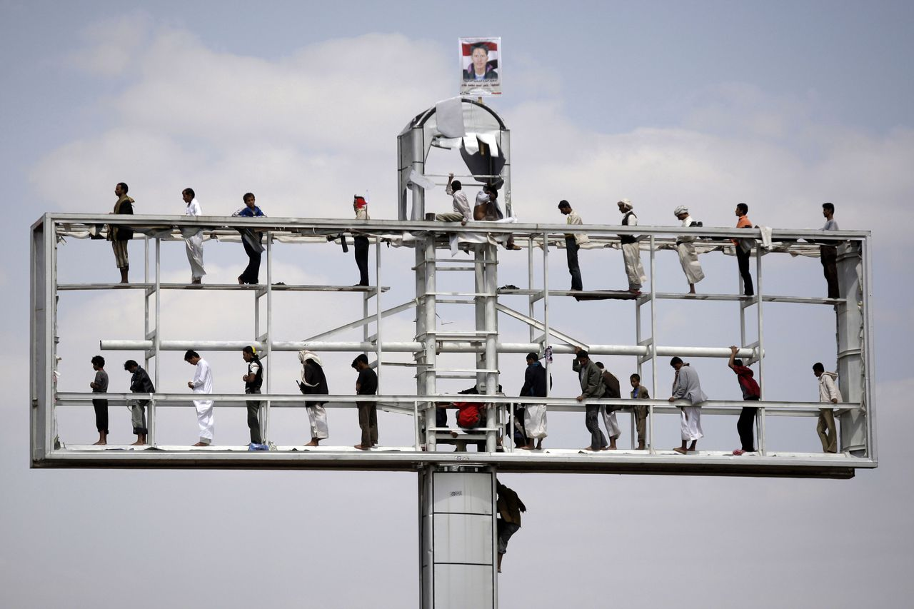 Protestors pray on a disused billboard during a demonstration to demand the resignation of Yemen's President Ali Abdullah Saleh in Sanaa, Yemen, Friday, Sept. 30, 2011. (AP Photo/Hani Mohammed)