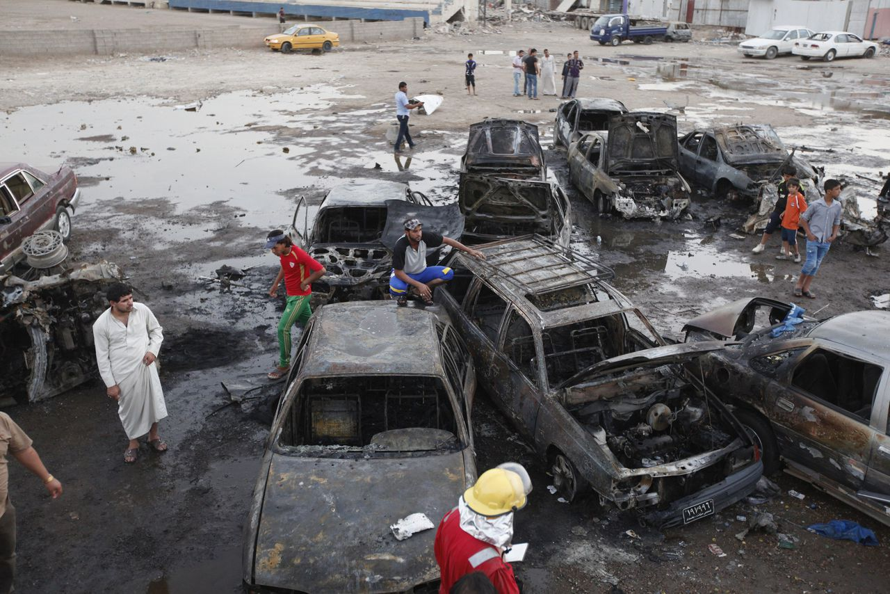 Residents gather at the site of bomb attacks in Baghdad May 27, 2013. More than 70 people were killed in a wave of bombings in markets in Shi'ite neighbourhoods across Baghdad on Monday in worsening sectarian violence in Iraq. REUTERS/Thaier al-Sudani (IRAQ - Tags: CIVIL UNREST POLITICS)