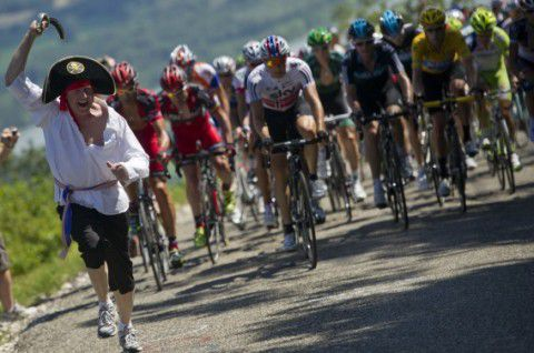 A fan disguised as a pirate runs next to overall leader's yellow jersey, British Bradley Wiggins riding in the pack during the 194,5 km and tenth stage of the 2012 Tour de France cycling race starting in Macon and finishing in Bellegarde-sur-Valserine, center eastern France, on July 11, 2012. AFP PHOTO / LIONEL BONAVENTURE
