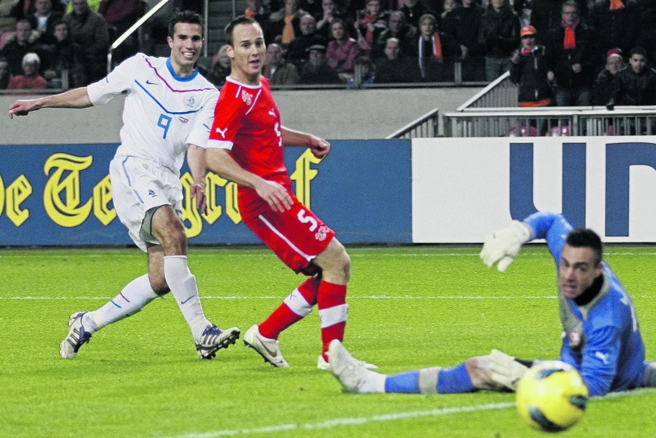 Robin van Persie of the Netherlands, left, tries to score passing Steve Von Bergen, center, and goalkeeper Diego Benaglio of Switzerland during the international friendly game at ArenA stadium in Amsterdam, Netherlands, Friday Nov. 11, 2011. (AP Photo/Peter Dejong)