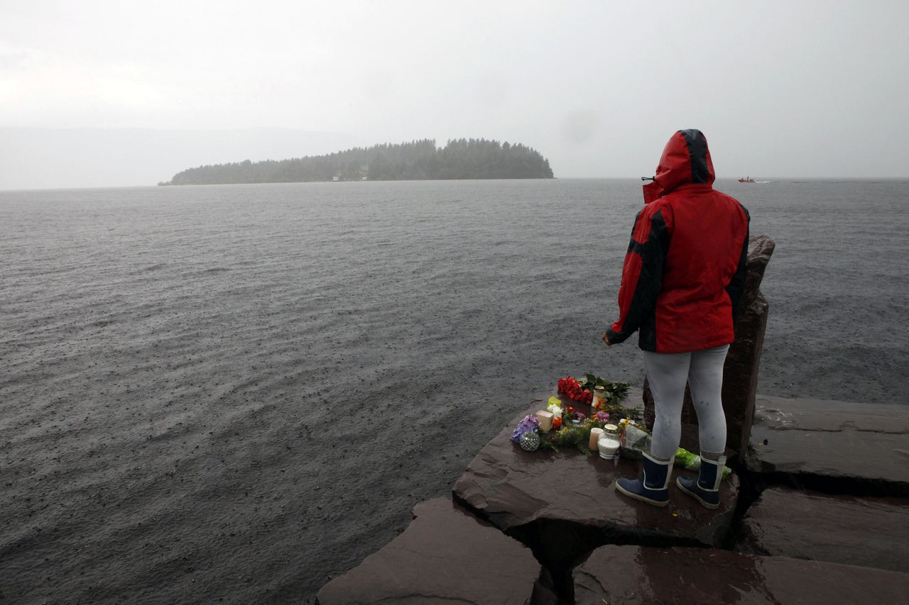 A woman stands on the shore in front of Utoeya island, northwest of Oslo, July 24, 2011. At least 92 people are dead after a gunman dressed in police uniform opened fire at a youth camp of Norway's ruling political party on Friday in Utoeya island, hours after a bomb blast in the government district in the capital Oslo. According to local media, four or five participants at the youth camp are still unaccounted for. REUTERS/Fabrizio Bensch (NORWAY - Tags: CIVIL UNREST CRIME LAW)